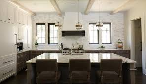 white and brown kitchen features white upper cabinets and brown distressed lower cabinets paired with fantasy brown granite countertops and a linear marble