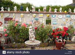a patio garden or back yard full of plastic gnomes and other statues wales uk