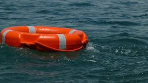 Low angle footage of a red rescue buoy floating on the water surface/A red