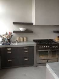 light colored creamy concrete countertops and a backsplash for a contrast with dark stained cabinets