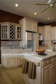 kitchen light stained wood cabinets dark red walls wine rack corner of