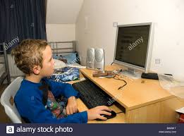 a young boy on his puter in an untidy bedroom stock image
