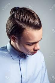 トップノット髪型と若い男の側上面の肖像画スタジオ撮影します の
