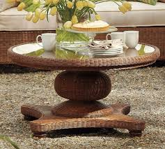 round rattan coffee table with white tulip flower centerpiece on glass top decor