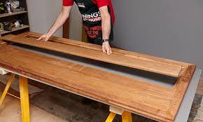 diy wooden outdoor table. person placing decking in frame diy wooden outdoor table