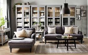 a living room with a grey three seat sofa chaise lounge and a black round coffee table bined with four grey gl door cabinets