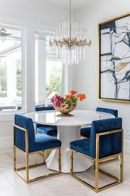 a round white dining table finished with gold and blue sapphire dining chairs under a br