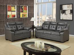 shiny charcoal apartment size sectional leather sofa with recliner and matching loveseat plus oval coffee table on cream wood floor