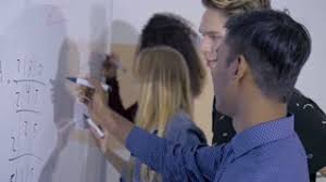 college classroom whiteboard. college students writing on a whiteboard in the classroom. diverse group of pupils studying together classroom n