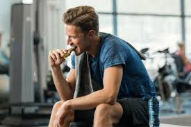 man eating protein bar at the gym