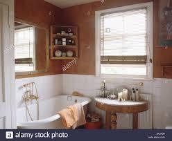 washstand bathroom pine: antique washstand in bathroom with pine corner shelves above white clawfoot bath tortoiseshell paint effect walls