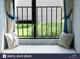 Stock Photo - resting area of a cozy window seat with green cushion in the  morning horizontal composition