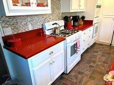 Kitchen remodel - White cabinets with smoked glass, polished silver  hardware and red Caesarstone counter