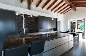 modern kitchen with white cabinets and black granite countertops and granite backsplash