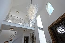 large modern chandelier hanging from vaulted ceiling