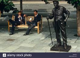 suits office. Two Young Men Dressed In Office Suits Alongside The Statue Of Traditional Working Man Flat Cap And Hobnailed Boots. R
