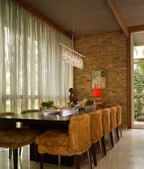 view in gallery cozy and inviting dining room with exposed brick wall a long table and soft chair