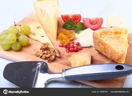 assortment of cheese with fruits gs nuts and cheese knife on a wooden serving tray photo by vicby