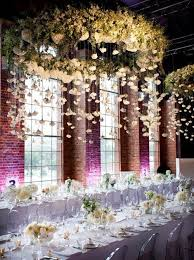 giant white flower chandelier with hanging flowers from above for an all white modern reception