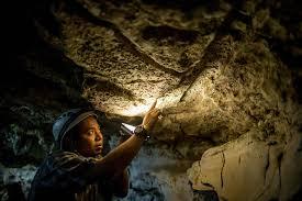 an indonesian archaeologist examines art inside leang timpuseng justin mott