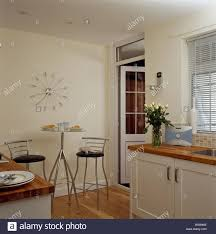 Modern Stainless Steel Clock On Wall Above Small Stainless Steel