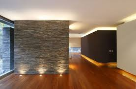 outstanding interior look of casa casuarinas with stone wall white ceiling wooden floor and bright lighting