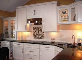 ... Compact corner sink in a kitchen with dark countertop and white cabinets