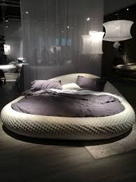 grey round bed with purple bedding
