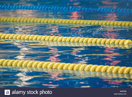 lanes in swimming pool with clean blue water reflection on blue pool water stock