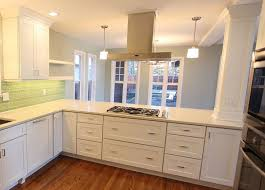 kitchen peninsula with cooktop, stainless range hood and pillar with crown  molding.