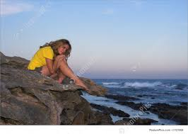lonely attractive sitting on a rock at the beach