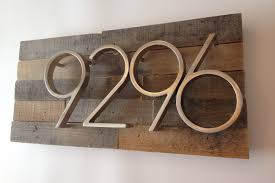 traditional art deco house numbers with wood and metal numbers on white wall decorated in front