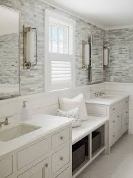 white bathroom cabinets gray walls. calming master bathroom with shiplap and tile walls, a window seat flanked by his her sinks, light gray cabinets silver hardware sophie metz design white walls n