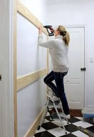 a homeowner nails boards to the wall a few steps later this entryway organizing idea is gorgeous