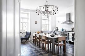 above a kitchen that stands ready for dinner parties the light filled space features a modern chandelier marble top table stainless steel appliances