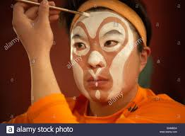 performer applying face paint with brush stock image