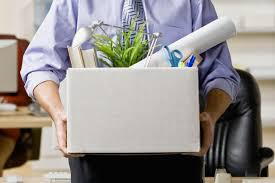 the difference between being fired and getting laid off office worker carrying box of belongings