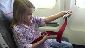 4k young girl in plane learning safety belt seat belt child travelling airplane kid suffering by flying sickness people tourists aboard in vacation