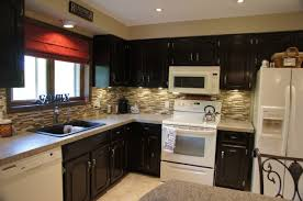 black color staining oak kitchen cabinets with white appliances and granite countertop plus false stone cladding backsplash small kitchen spaces ideas