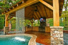 amazing fireplace on deck with beautiful swimming pool and waterfall also using ceiling fan and tv