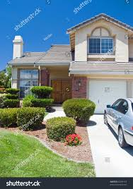 New American dream home with a beautiful blue sky in background and brand  new car parked