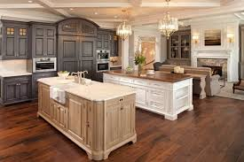 single wall great room kitchen with coffered ceiling chandelier farmhouse sink and 2 islands