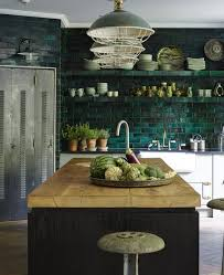 a dark green tile backsplash is extended on the whole wall and green lamps echo