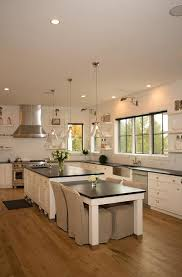 two glass cone shaped pendants hang over a white kitchen island topped with soapstone fitted with a prep sink next to a drop down soapstone top dining table