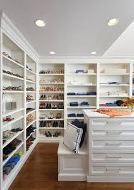 custom walk in closet features walls lined with floor to ceiling white modular shoe and jean shelves lit by recessed lighting and facing a white island