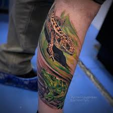 фото цветной мужской татуировки в стиле реализм на ноге ящерица и