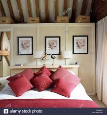 Modern Country Bedroom Pictures On White Panelled Wall Above Bed With Red Cushions In