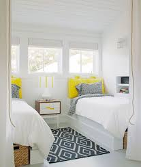 view in gallery very white guest room with bright yellow twin bed pillows