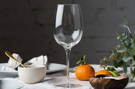 our pick wine glass on a table decorated with plants plates and