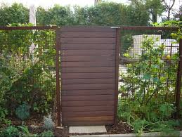 gate of horizontal boards framed by a hogwire fence image via environmental concepts for more of our picks see 10 easy pieces wooden garden gates